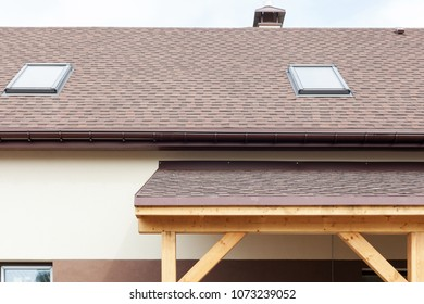 Window skylight on a roof with asphalt shingles or bitumen tiles under construction.