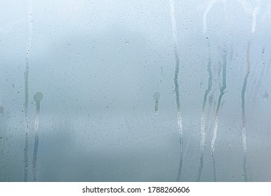 Window with steam condensation and drops after rain, wet glass as background or texture