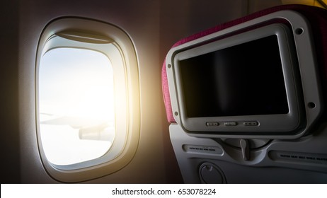 Window with sunlight and Private monitor on airplane seat to entertainment service for passenger in travel concept.