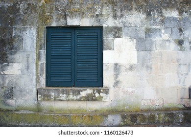 Window with turqiouse closed shutters on the colorful textured stone wall