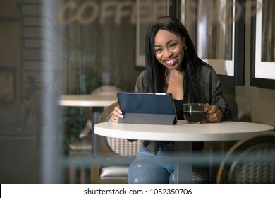 Window view of a black female using a tablet connected to wifi internet in a coffeeshop.  The businesswoman or student is taking a break or working and studying at the cafe.