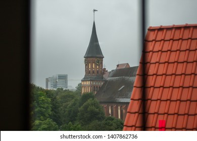 The window view of the Kaliningrad cathedral behind the roof on the grey sky background. Kaliningrad architecture background