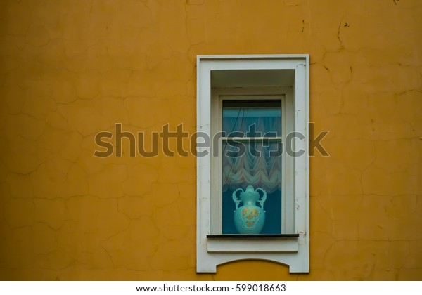 Window with a  vintage vase on the yellow wall