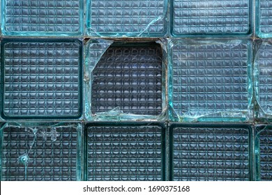 A window in a wall of broken glass blocks in a house destroyed after an accident. Creative trendy vintage background broken glass blocks