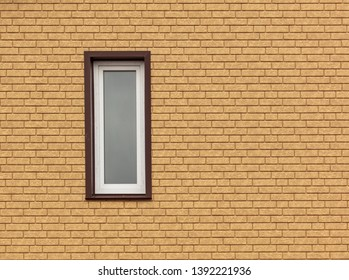 The window in the wall of the house of yellow brick.