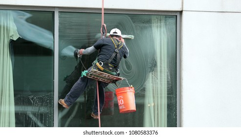 Window washer cleaning building facade. Person cleaning building window