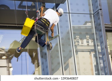 Window washer cleaning the windows of shopping center