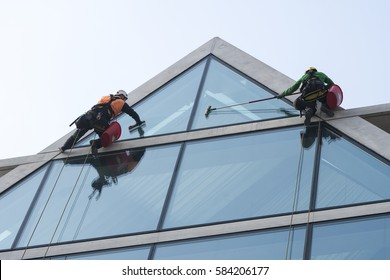 Window washers cleaning the glass facade of a modern building, high risk work.