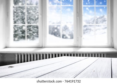 Window with winter landscape and snow. White wooden table of free space for your decoration.