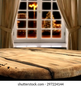 window of winter with xmas tree on street in city and empty wooden big table place