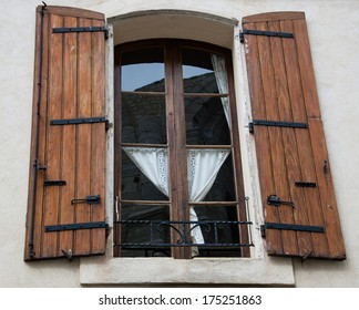 Window with wooden hinged shutters and white lace curtain and the reflection of a Roman Arena of Arles. (Bouches-du-Rhone, Provence-Alpes-Cote d'Azur, France)