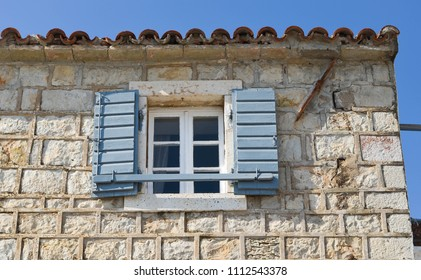 Window with wooden shutters on the rustic stone wall.  Mediterranean house.