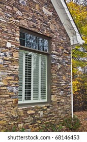 Window with wooden shutters in the stone facade of a house.