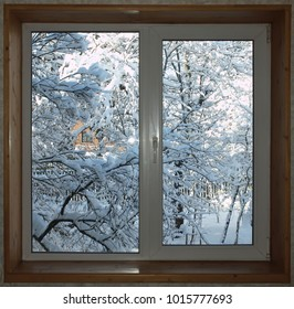 Window with a wooden window sill overlooking the snow-covered garden.