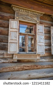 Window in wooden wall of house of nineteenth century in Russia
