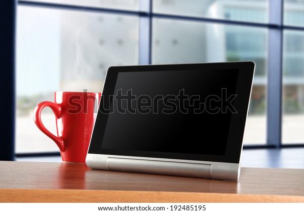 window yellow top and mug with tablet