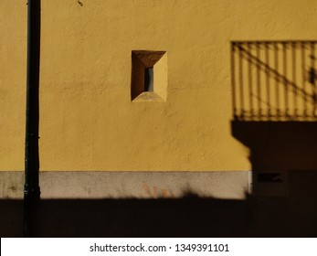 Window in yellow wall with balcony shadow.