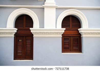 windowBig and small with wooden shutters on grey wall background in San Juan, Puerto Rico. House with plastered facade. Asymmetry and urban geometry concept. Construction and renovation.