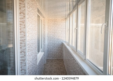Windowed balcony, decorated with paneling and granitic tiles on the floor.