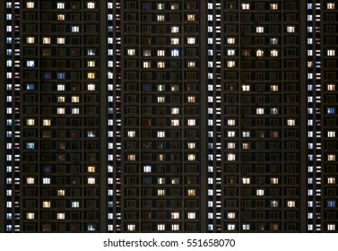 windows of an apartment building glow in the dark