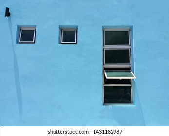 Windows awning with vintage sky blue concrete wall texture . Concrete wall painted in sky blue as a background. Exterior and Interiors decor.   Ventilation, Lighting, and Energy saving concept.