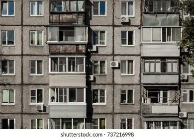 Windows and balconies of a dilapidated house made of concrete. Several floors, many apartments. Bad living conditions, terrible housing, cheap rooms.