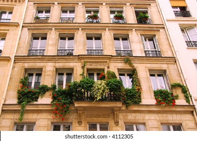 Windows and balcony covered by ivy on a building in Paris France