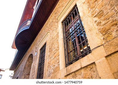 Windows with bars in a stone house. The house is built of brown colored stone blocks. The windows of the old house are closed with metal bars.