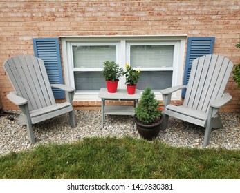 windows and blue shutters and chairs and plants and rocks