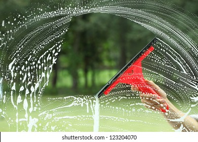 Windows cleaning, glass without smudges red squeegee