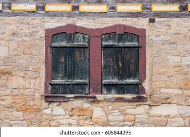 Windows with closed shutters in a medievil sandstone wall
