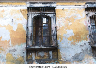 Windows and faded paint on an old building wall in Antigua, Guatemala, Central America.