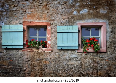 windows with flower decoration in the textured brickwork wall