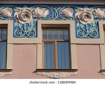 Windows and a fragment of the facade, decorated with stucco roses, in the style of art nouveau