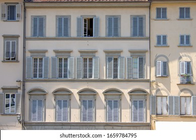 Windows with grey wooden shutters and a typical Italian house facade.