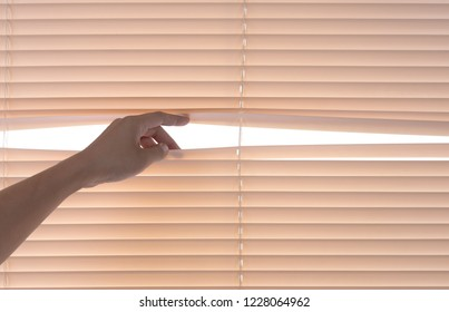Windows jalousie,hand separating slats of venetian blinds with a finger to see through