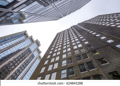 Windows of a modern office building reflects an old brick of building in  downtown Toronto Canada.