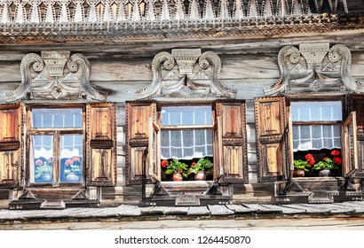 Windows of old Russian log house with carved wooden platbands. Vintage traditional wooden house with carved ornament