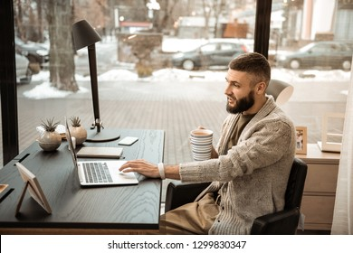 Windows on background . Expressive bearded man with cup of coffee in his hands working on slim laptop