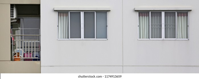 Windows on the outside of a apartment with small balcony.