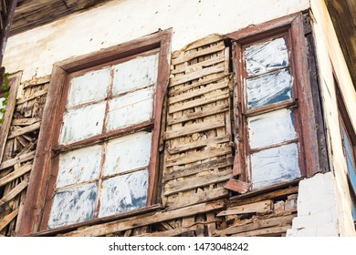 The windows are painted white. The walls of the house are very destroyed from old age. The house is no longer suitable for living.
