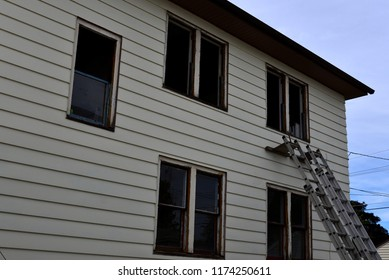 Windows removed from a two story house in preparation for replacements.