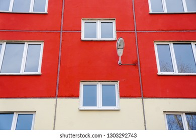 The windows of a residential building on a yellow and red background, street lamp, perfectionism, texture.