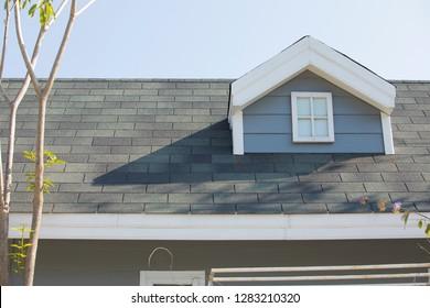 windows at the roof of the house,new roof under construction,Roof shingles on top of the house against sky
