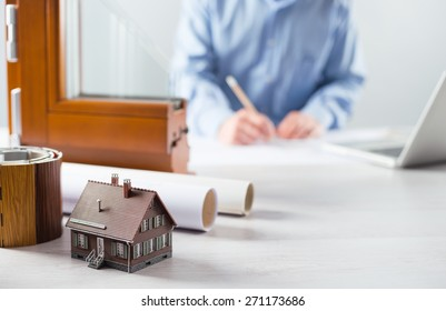 Windows section with triple glazing and wooden frame and man working on a house project with laptop on background