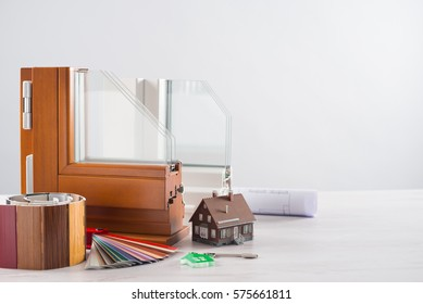 Windows section with triple glazing and wooden frame, shutters swatches, house model and keys, home renovation concept