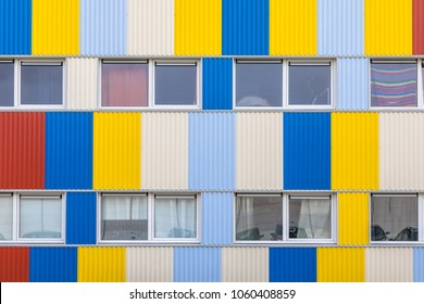 Windows of Student housing in shipping containers painted in pright colors with bicycle parking in the foreground