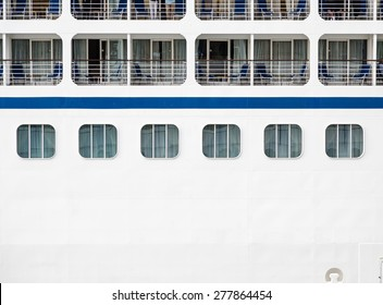 Windows, verandas and decks on the side of a massive luxury cruise ship