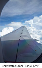 Windows view of flight on wing side of the plane through storm with lighting on sky