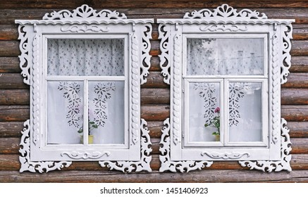Windows with white carved frames in the old wooden house.
